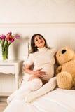 Zwangere vrouw die haar buik houden Stock Fotografie