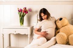 Zwangere vrouw die haar buik houden Stock Afbeelding