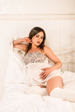 Zwangere vrouw die haar buik houden Royalty-vrije Stock Afbeeldingen