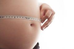 Zwangere vrouw die haar buik meet Stock Foto