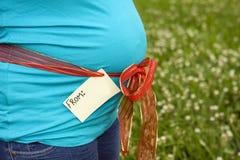 Zwangere vrouw die haar buik met een markering toont Stock Foto