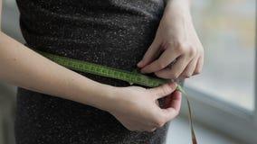 Zwangere vrouw die haar buik met meetlint meten stock footage