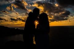 Zwangere vrouw die haar partner kussen bij zonsondergang vóór geboorte voor een photosession stock foto