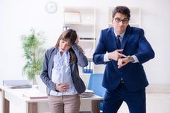 Zwangere vrouw die in het bureau worstelen en collega krijgen hij royalty-vrije stock foto's