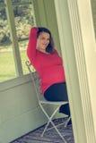 Zwangere vrouw die het rode overhemd stellen in tuinpergola dragen Royalty-vrije Stock Foto