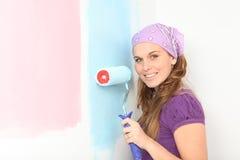 zwangere vrouw die kinderdagverblijfroze of blauw beslissen te schilderen Stock Afbeelding