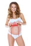 Zwangere vrouw die kleine babyhoed houdt Stock Fotografie