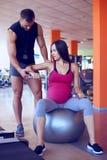 Zwangere vrouw die met persoonlijke trainer in gymnastiek uitoefenen stock foto's