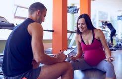 Zwangere vrouw die met persoonlijke trainer spreken stock afbeelding