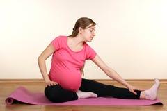 Zwangere vrouw die oefeningen doet royalty-vrije stock fotografie