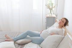 Zwangere vrouw die op bed ligt stock fotografie