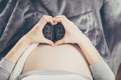 Zwangere vrouw die op de bank liggen en een hartvorm met Ha doen Stock Afbeeldingen