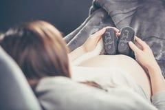Zwangere vrouw die op de bank liggen en schoenen ongeboren kind houden Royalty-vrije Stock Foto