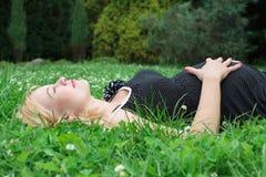 Zwangere vrouw die op het gras liggen royalty-vrije stock foto