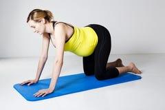 Zwangere vrouw die op mat knielt stock afbeelding