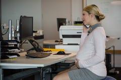 Zwangere vrouw die op mobiele telefoon bij bureau spreken stock afbeelding