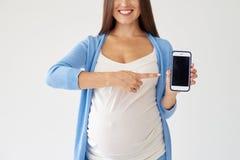 Zwangere vrouw die op smartphone met het zwarte scherm richten stock afbeeldingen
