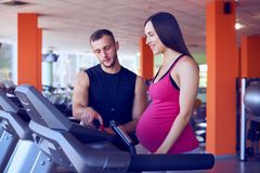 Zwangere vrouw die op tredmolen met persoonlijke trainer uitoefenen stock afbeelding