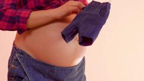 Zwangere vrouw die pasgeboren clothers in handen op haar grote naakte zwangere buik houden Zwanger wijfje dat een leuke baby houd stock video
