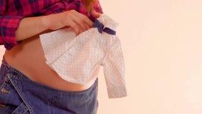 Zwangere vrouw die pasgeboren leuke clothers in handen op haar grote naakte zwangere buik houden Zwanger wijfje die leuk houden stock video