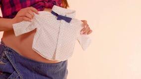 Zwangere vrouw die pasgeboren leuke clothers in handen op haar grote naakte zwangere buik houden Zwanger wijfje die leuk houden stock videobeelden