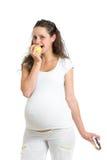 Zwangere vrouw die tussen gezonde voedselvruchten en cake ISO kiezen Stock Fotografie