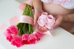 Zwangere vrouw die uiterst kleine roze kindsokken in handen met liefde houden Stock Afbeelding