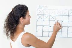 Zwangere vrouw die van data op kalender merken Stock Foto