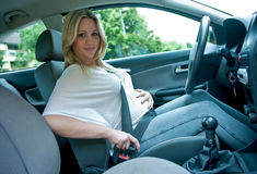 Zwangere vrouw die veiligheidsgordel met behulp van Royalty-vrije Stock Afbeeldingen