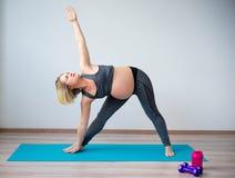 Zwangere vrouw die yoga doet stock afbeelding