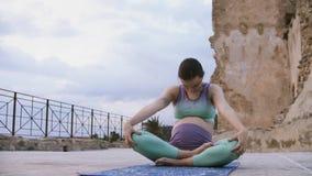 Zwangere vrouw die yoga doet Aanstaande moederpraktijk ademhalingsoefeningen stock videobeelden
