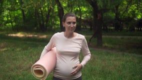 Zwangere vrouw die yoga doet Een meisje loopt met een deken in haar hand, dan werpend de deken op het gras aan begin het praktize stock video