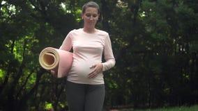 Zwangere vrouw die yoga doet Een meisje loopt met een deken in haar hand, dan werpend de deken op het gras aan begin het praktize stock footage