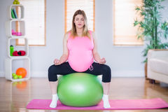 Zwangere vrouw die yoga op oefeningsbal doen Stock Afbeelding