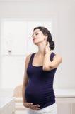 Zwangere vrouw die zich met een pijn in de hals bevinden Stock Afbeeldingen