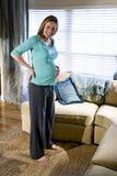 Zwangere vrouw die zich in woonkamer bevindt stock foto