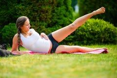 Zwangere Vrouw die Zij het Doen leunen Beenlift in Park uitvoeren stock foto's