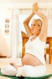 Zwangere vrouw die zwangerschapsyoga doet Royalty-vrije Stock Afbeeldingen