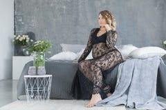 Zwangere vrouw in een mooie zitting van de kantkleding op het bed stock foto