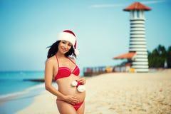 Zwangere vrouw in een rood badpak en een hoed van Kerstmissanta op de overzeese kust stock foto