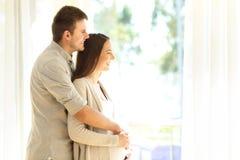 Zwangere vrouw en echtgenoot die trogvenster kijken royalty-vrije stock foto's