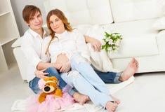 Zwangere vrouw en een man in wit stock fotografie