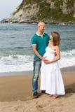 Zwangere vrouw en haar echtgenoot die door het overzees wandelen. Stock Afbeelding
