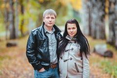 Zwangere vrouw en haar echtgenoot die in het de herfstpark lopen Stock Foto's