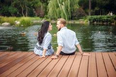 Zwangere vrouw en haar echtgenoot in een park dichtbij water het koesteren stock afbeelding