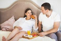 Zwangere vrouw en man die ontbijt met jus d'orange en Cr hebben royalty-vrije stock afbeelding