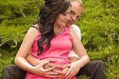 Zwangere vrouw in groene tuin Stock Afbeeldingen