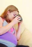 Zwangere vrouw het drinken thee op bank royalty-vrije stock afbeelding