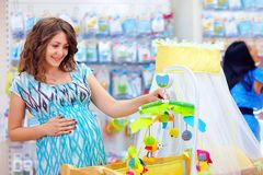 Zwangere vrouw het kopen wieg met mobiel stuk speelgoed voor baby Stock Fotografie