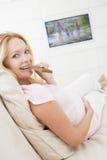 Zwangere vrouw het letten op televisie en het eten choc stock afbeeldingen